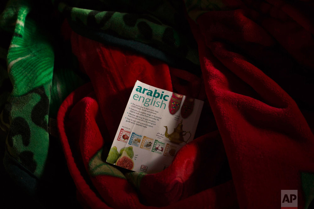 """In this Thursday, Oct. 27, 2016 photo, a dictionary remains over other belongings left behind by migrants in an abandoned tent at the makeshift migrant camp known as """"the jungle"""" near Calais, northern France. (AP Photo/Emilio Morenatti)"""