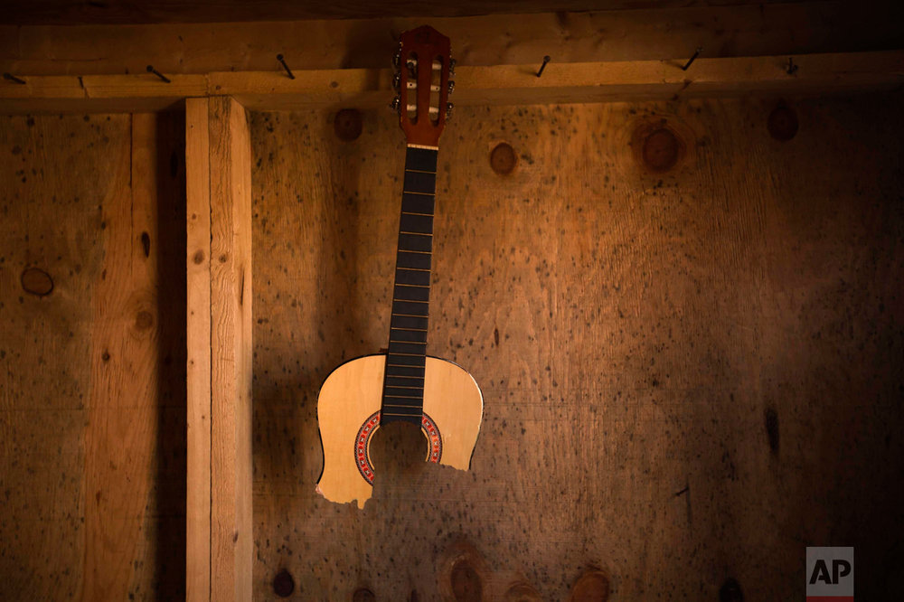 """In this Thursday, Oct. 27, 2016 photo, a broken guitar hangs in an abandoned tent at the makeshift migrant camp known as """"the jungle"""" near Calais, northern France. (AP Photo/Emilio Morenatti)"""
