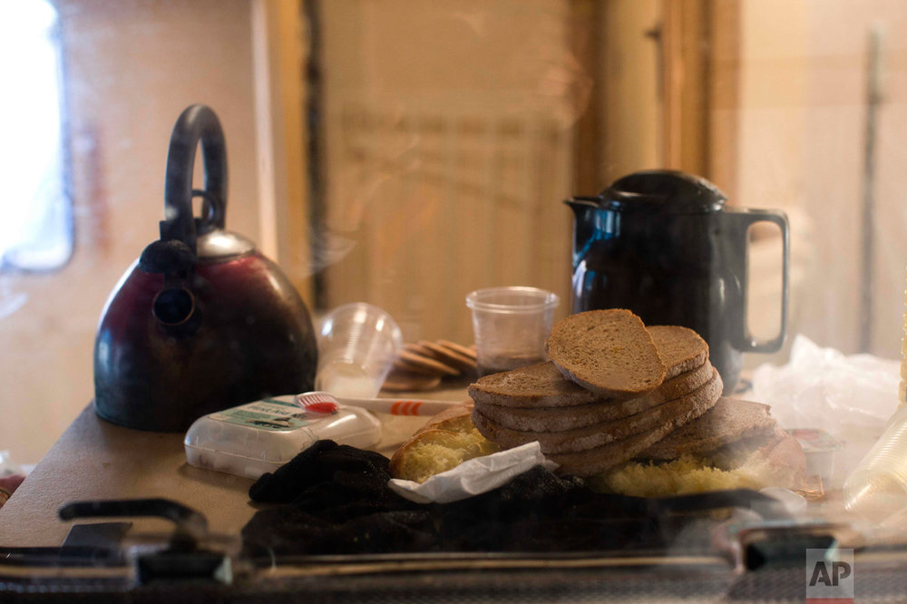 """In this Thursday, Oct. 27, 2016 photo, bread and coffee is left behind by migrants in an abandoned caravan at the makeshift migrant camp known as """"the jungle"""" near Calais, northern France. (AP Photo/Emilio Morenatti)"""
