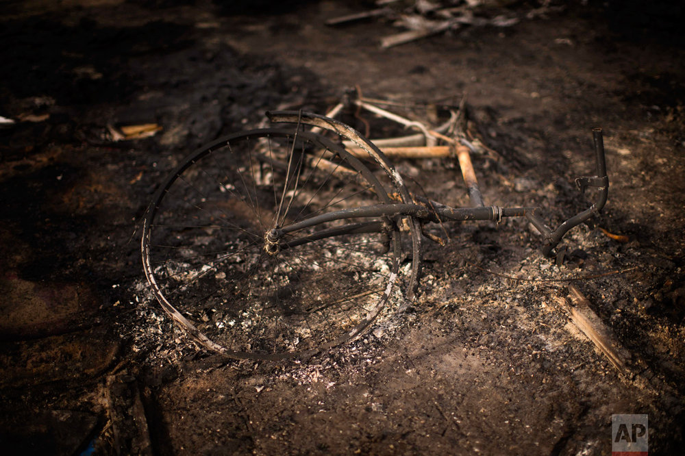 """In this Thursday, Oct. 27, 2016 photo, a burnt bicycle remains on the floor of a charred tent at the makeshift migrant camp known as """"the jungle"""" near Calais, northern France. (AP Photo/Emilio Morenatti)"""