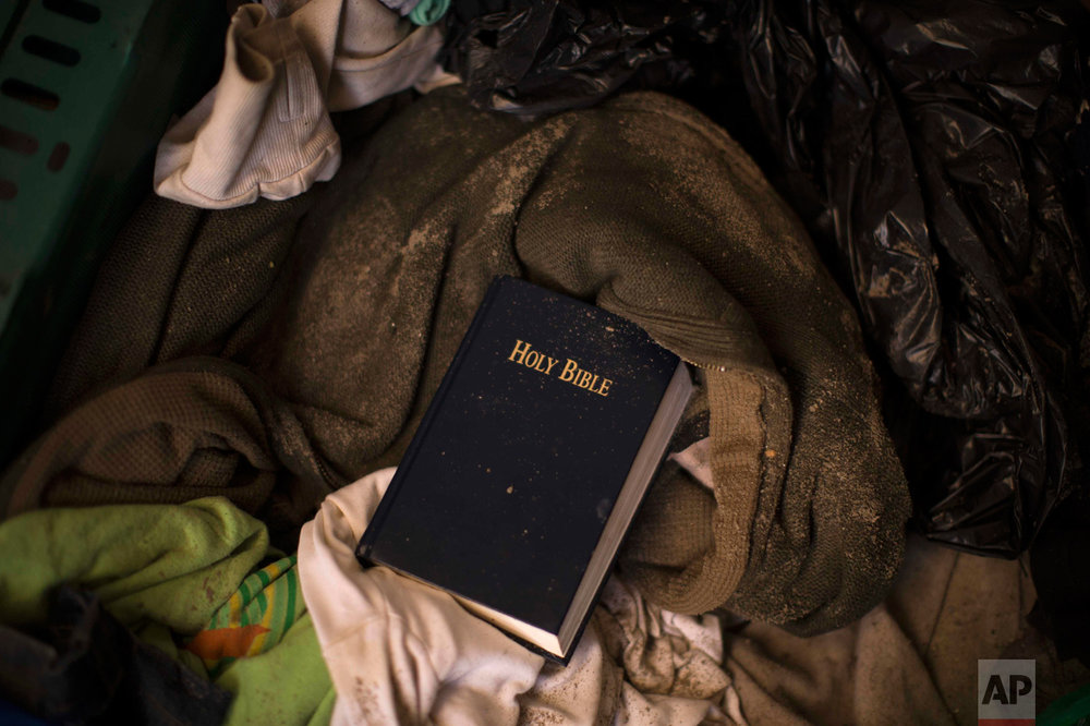 """In this Thursday, Oct. 27, 2016 photo, a copy of the Bible remains over other belongings left behind by migrants, in an abandoned tent at the makeshift migrant camp known as """"the jungle"""" near Calais, northern France. (AP Photo/Emilio Morenatti)"""