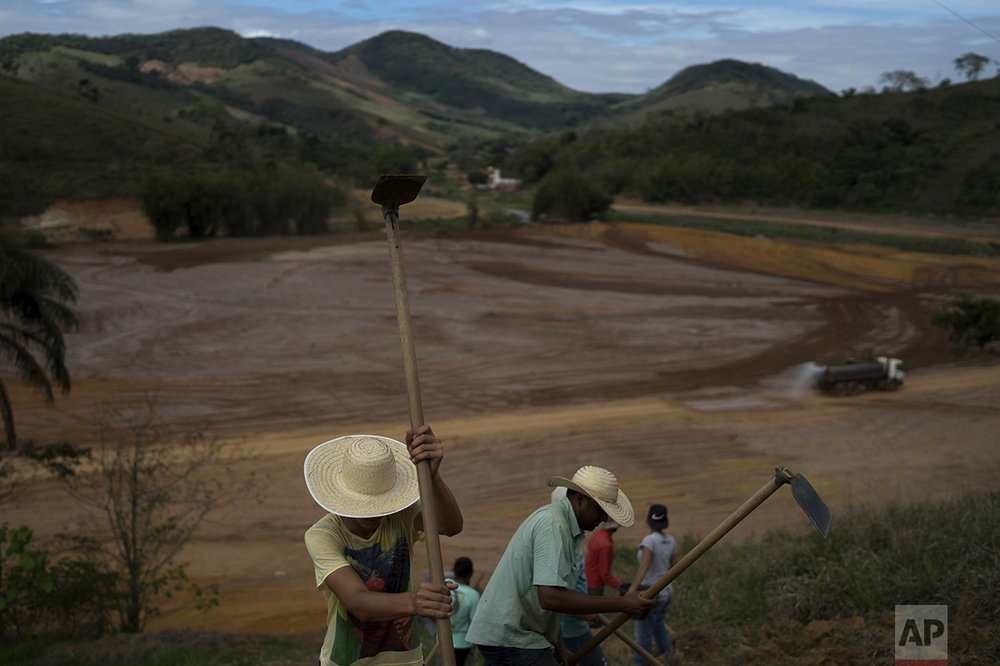 In this Oct. 13, 2016 photo, employees prepare a slope to prevent erosion that could be caused by the expected rain this time of the year along the Doce River, almost a year after a dam holding back a giant pond of mine waste broke open, in Gesteira, Brazil. Officials worry the rainy season may further eat away riverbanks by spreading the waste still in the basin. (AP Photo/Leo Correa)