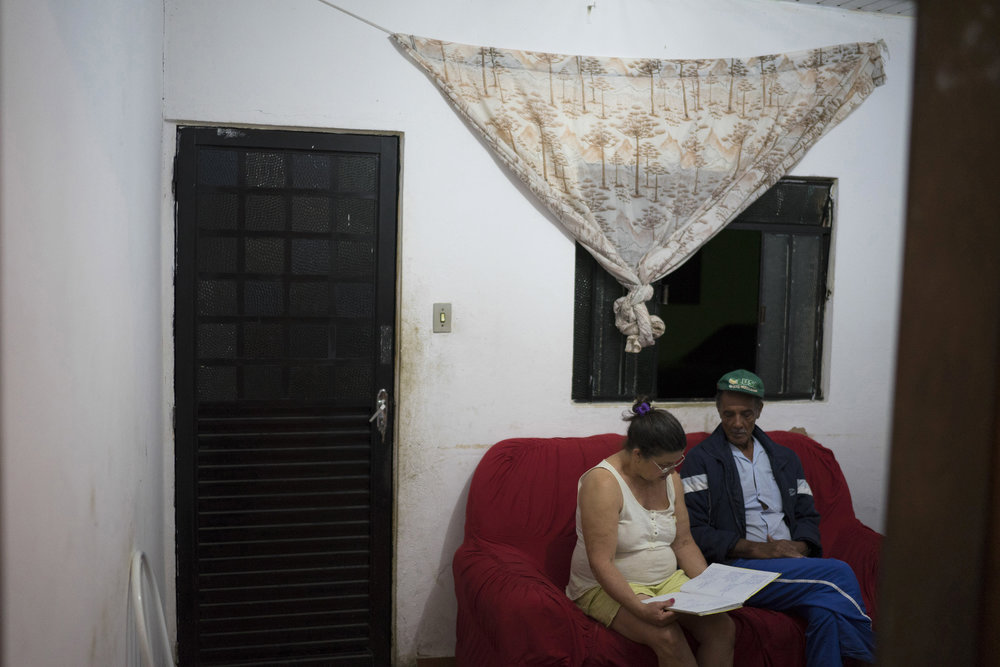 "In this Oct. 13, 2016 photo, Maria do Carmo Pereira Ramos, left, sits next to her husband Jose do Patrocinio de Oliveira, in Mariana, Brazil, as she reads aloud a poem she wrote about the tragedy of their hometown. She wrote, ""With sadness in our heart we left our place, where we raised our sons, and the homesickness will stay. Paracatu and Bento Rodrigues in the history will stay, we may go back one day, but it never again will be the same."" (AP Photo/Leo Correa)"