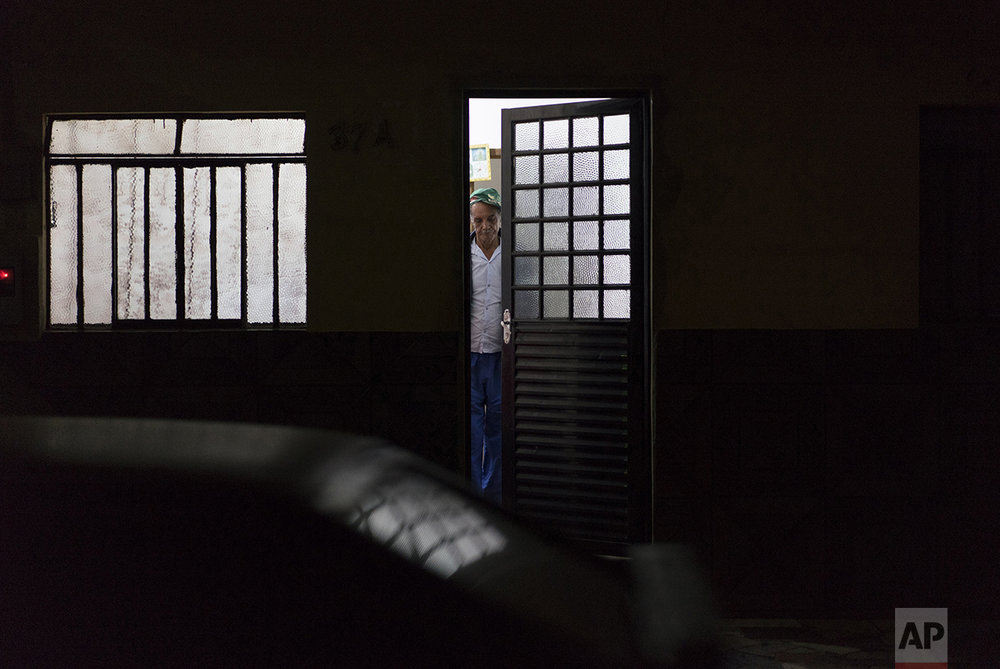 In this Oct. 13, 2016 photo, Jose do Patrocinio de Oliveira closes the front door to his apartment, in Mariana, Brazil. People who lost their homes in the villages wrecked by a Nov. 5, 2015 tsunami of mud are living all across the cobbled-stone city of Mariana, waiting to be relocated to new rural areas. Many say they feel like prisoners in their temporary city apartments. (AP Photo/Leo Correa)