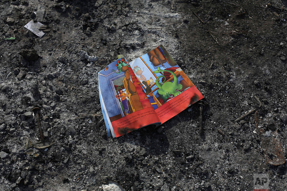 """In this Thursday, Oct. 27, 2016 photo, a child's book left behind on the floor of a shelter by migrants in an abandoned tent at the makeshift migrant camp known as """"the jungle"""" near Calais, northern France. (AP Photo/Thibault Camus)"""