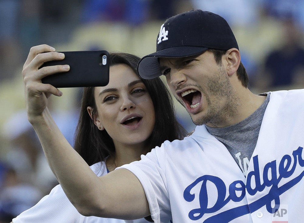 Ashton Kutcher and wife Mila Kunis take a selfie before Game 4 of the National League baseball championship series between the Chicago Cubs and the Los Angeles Dodgers Wednesday, Oct. 19, 2016, in Los Angeles. (AP Photo/David J. Phillip)