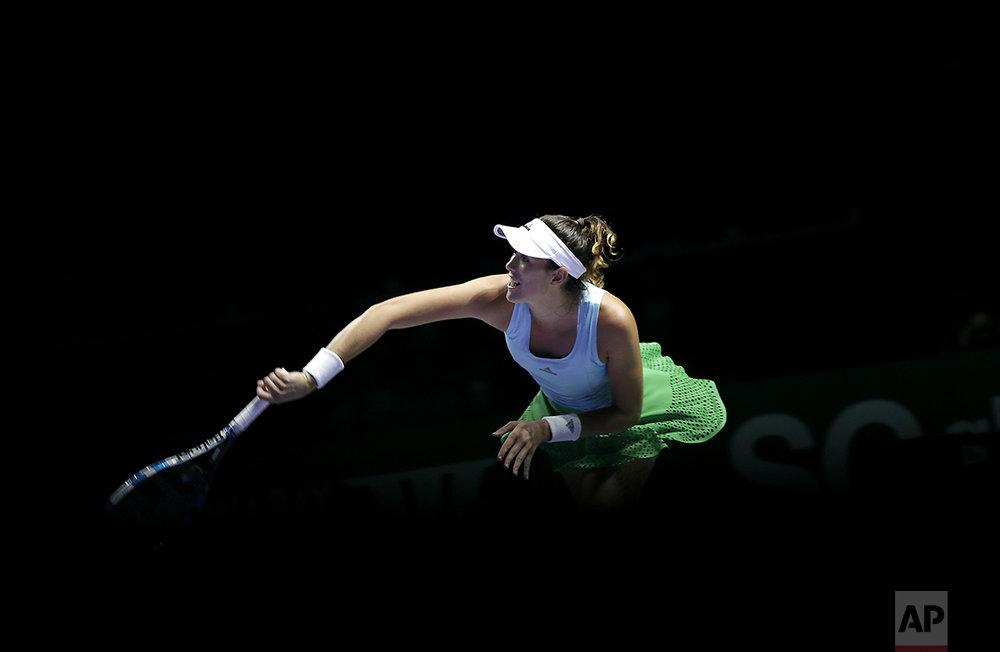 Garbine Muguruza, of Spain, serves the ball to Karolina Pliskova, of the Czech Republic, during their singles match at the WTA tennis tournament in Singapore, Monday, Oct. 24, 2016. (AP Photo/Wong Maye-E)