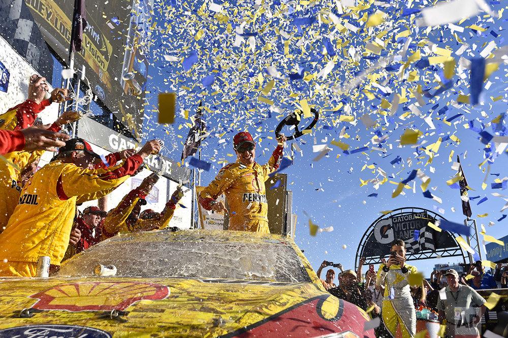 Joey Logano (22) celebrates after winning a NASCAR Sprint Cup Series auto race at Talladega Superspeedway, Sunday, Oct. 23, 2016, in Talladega, Ala. (AP Photo/Matthew Bishop)