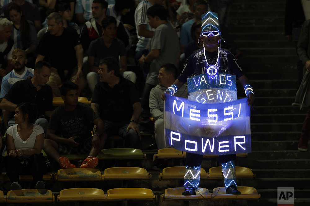 An Argentina fan holds a national flag with a lighted sign in support of star player Lionel Messi, prior a 2018 World Cup qualifying soccer match against Paraguay, in Cordoba, Argentina, Tuesday, Oct. 11, 2016. (AP Photo/Natacha Pisarenko)