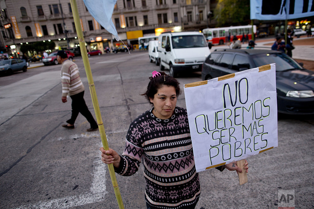 "In this Oct. 5, 2016 photo, Ana Paz holds a sign that reads in Spanish ""We don't want to be poorer"" as she protests outside Congress, near a soup kitchen in Buenos Aires, Argentina. President Mauricio Macri's market-friendly reforms have been praised by international investors, who say they lay the groundwork for growth. But so far, they've brought only pain to the country's poor. (AP Photo/Natacha Pisarenko)"