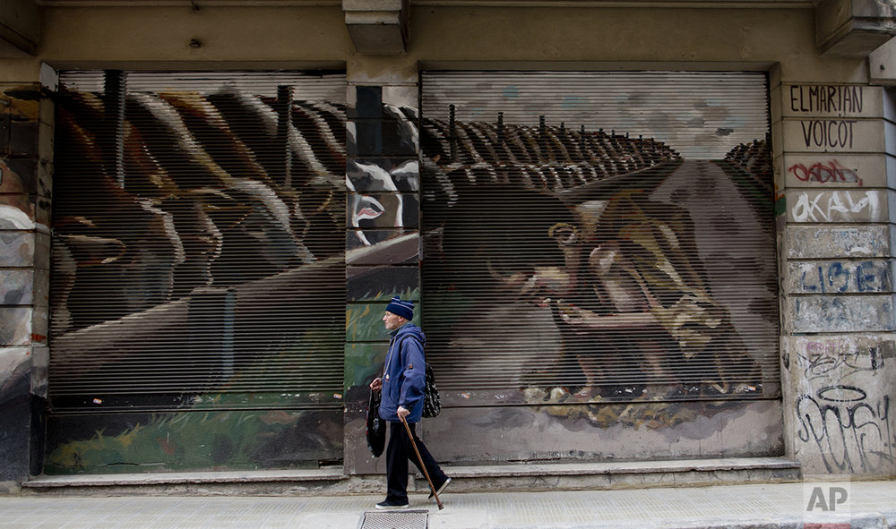 "This Oct. 5, 2016 photo shows a mural titled ""Hunger Games"" by artist El Marian, featuring a starving boy huddling next to cattle eating grain in Buenos Aires, Argentina. The mural was an idea from animal rights group ""Voicot"" and aims to call attention to Argentina being one of the world's top grain producers, and that most of it is used to feed livestock. (AP Photo/Natacha Pisarenko)"