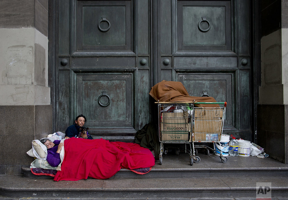 "In this Oct. 5, 2016 photo, Maria Susana Silveira, 55, and Jorge Fernandez, 46, who live in the street as a team, rest outside Banco Nacion with their dog Toto, across the street from La Casa Rosada presidential house in Buenos Aires, Argentina. ""In the past nine months, about 1.5 million people have joined the ranks of the poor,"" said Lucila de Ponti, an opposition lawmaker leading the fight for a stimulus bill meant to create 1 million jobs. (AP Photo/Natacha Pisarenko)"