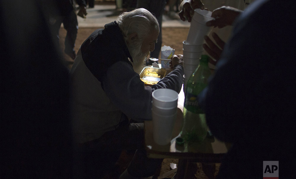 In this Oct. 5, 2016 photo, a homeless man eats free dinner at a soup kitchen set up on the sidewalk outside Congress in Buenos Aires, Argentina. Organizers set up their soup kitchen outside the legislature to make as statement to the government about poverty in the city. (AP Photo/Natacha Pisarenko)