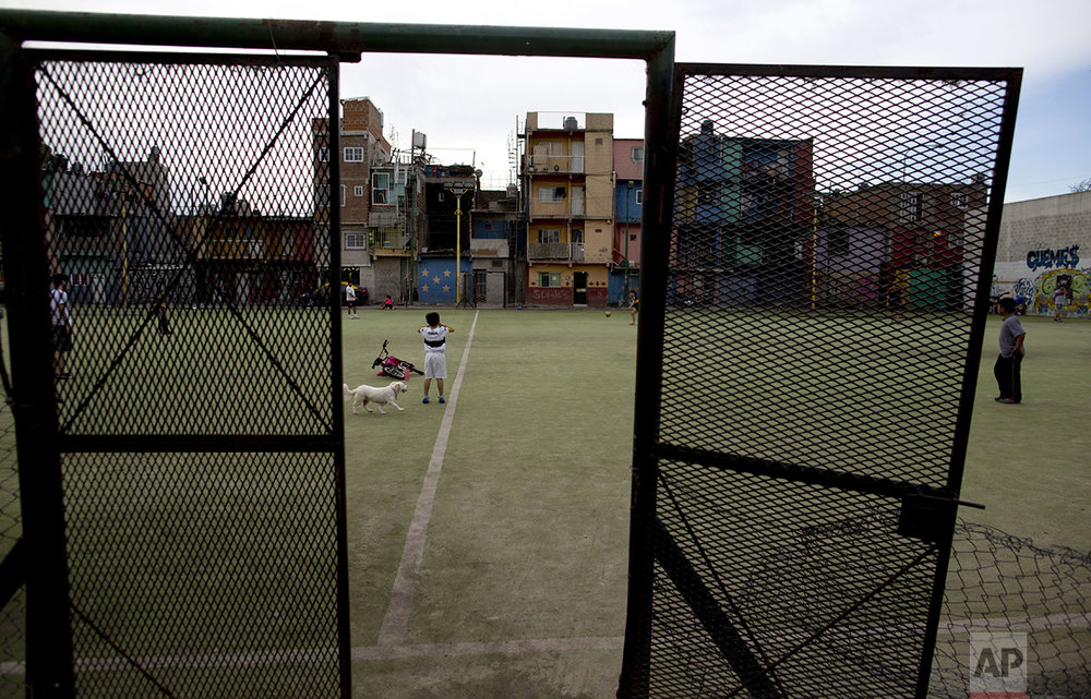 In this Oct. 13, 2016, kids play soccer in the Villa 31 neighborhood of Buenos Aires, Argentina. President Mauricio Macri's market-friendly reforms have been praised by international investors, who say they lay the groundwork for growth. But so far, they've brought only pain to the country's poor. (AP Photo/Natacha Pisarenko)