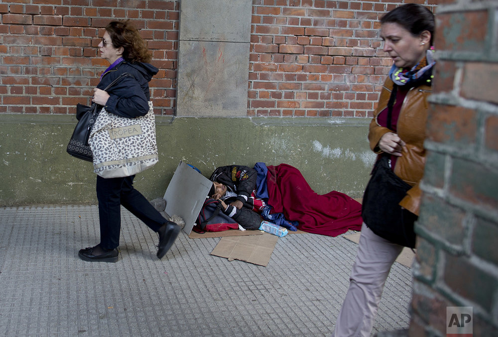 "In this Oct. 4, 2016 photo, women walk by a man sleeping on the sidewalk in Buenos Aires, Argentina. As President Mauricio Macri campaigned last year, he often said his goal was to reach ""zero poverty"" by the end of his term in 2019. But when he released the poverty figures in late September, he said it's obvious it won't be possible. (AP Photo/Natacha Pisarenko)"