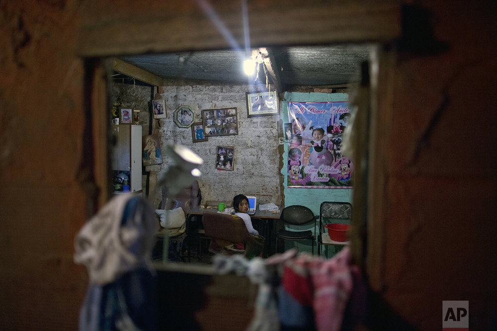 In this Oct. 13, 2016 photo, a girl looks over her shoulder as she does her homework in the Villa 31 neighborhood of Buenos Aires, Argentina. The government says more than 32 percent of Argentines live in poverty, unable to afford a basic basket of goods. (AP Photo/Natacha Pisarenko)