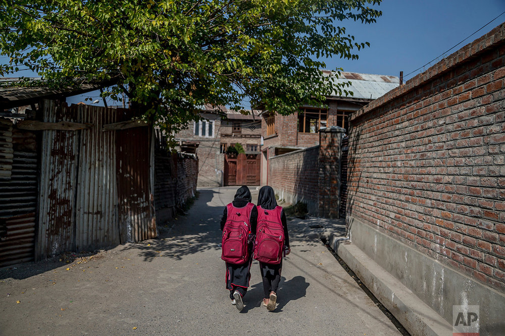 In this Thursday, Oct. 20, 2016 photo, Iqra, left and her cousin Muskan walk back home after attending an ad-hoc learning center set up in a local mosque in Srinagar, Indian controlled Kashmir. With daily life still paralyzed by strikes and rolling curfews, dozens of learning centers have popped up in people's homes or religious centers like mosques in Kashmir since August. The centers are doing more than just helping students prepare for upcoming exams, organizers said. They're keeping kids off the streets and giving them comfort amid a civilian uprising sparked when a popular rebel leader was killed in fighting Indian forces on July 8. (AP Photo/Dar Yasin)