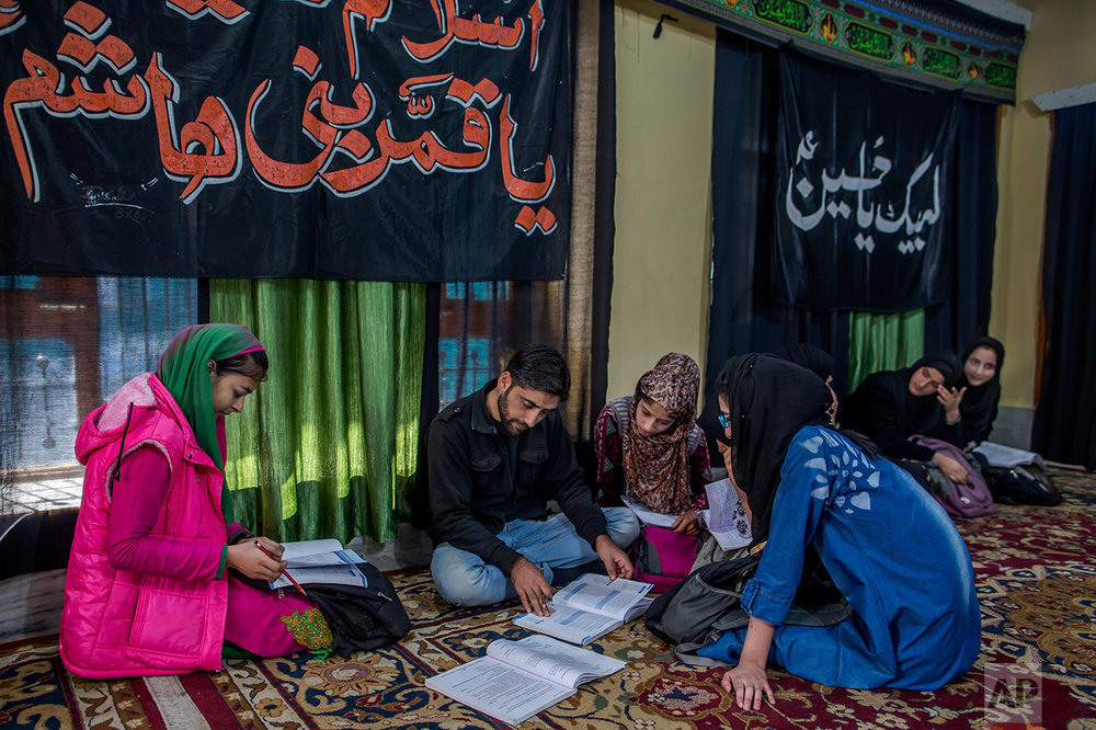 In this Wednesday, Oct. 19, 2016 photo, Mohammad Hussain teaches Kashmiri girls in an ad-hoc learning center set up in a building meant for religious activity in Srinagar, Indian controlled Kashmir. With daily life still paralyzed by strikes and rolling curfews, dozens of learning centers have popped up in people's homes or religious centers like mosques in Kashmir since August. They gather during daylight hours, often sitting on the floor, to hear a teacher read aloud from a text or practice mathematical equations in a shared notebook. (AP Photo/Dar Yasin)