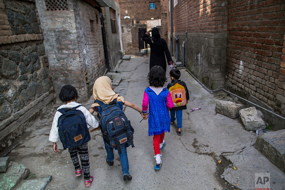 In this Friday, Oct. 7, 2016 photo, Kashmiri children walk home after attending an ad-hoc learning center set up in a community marriage hall in Srinagar, Indian controlled Kashmir. With daily life still paralyzed by strikes and rolling curfews, dozens of learning centers have popped up in people's homes or religious centers like mosques in Kashmir since August. The centers are doing more than just helping students prepare for upcoming exams, organizers said. They're keeping kids off the streets and giving them comfort amid a civilian uprising sparked when a popular rebel leader was killed in fighting Indian forces on July 8. (AP Photo/Dar Yasin)