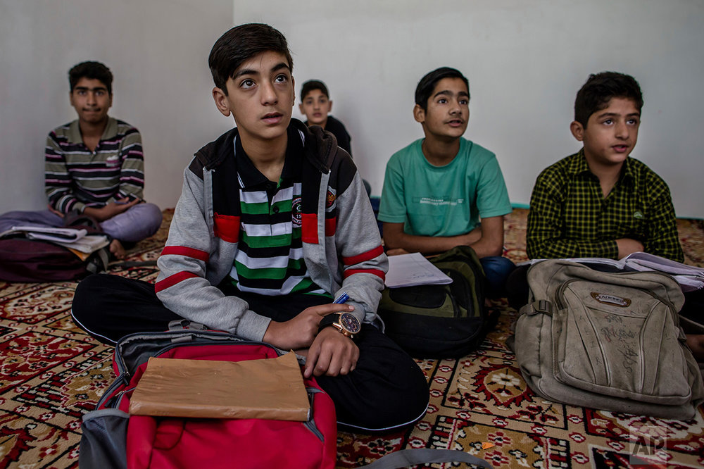 In this Thursday, Oct. 6, 2016 photo, Kashmiri boys study in an ad-hoc learning center set up in a community hall in Srinagar, Indian controlled Kashmir. With daily life still paralyzed by strikes and rolling curfews, dozens of learning centers have popped up in people's homes or religious centers like mosques in Kashmir since August. The centers are doing more than just helping students prepare for upcoming exams, organizers said. They're keeping kids off the streets and giving them comfort amid a civilian uprising sparked when a popular rebel leader was killed in fighting Indian forces on July 8. (AP Photo/Dar Yasin)