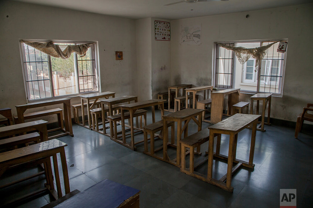 In this Tuesday, Oct. 18, 2016 photo, desks and benches stand in rows inside an empty classroom of a private school that has remained closed for the past three months in Srinagar, Indian controlled Kashmir. With daily life still paralyzed by strikes and rolling curfews, dozens of ad-hoc learning centers have popped up in people's homes or religious centers like mosques in Kashmir since August. The centers are doing more than just helping students prepare for upcoming exams, organizers said. They're keeping kids off the streets and giving them comfort amid a civilian uprising sparked when a popular rebel leader was killed in fighting Indian forces on July 8. (AP Photo/Dar Yasin)