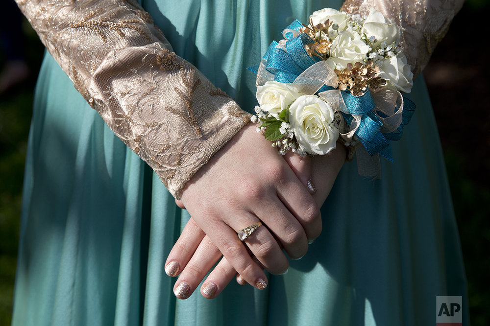Nails freshly manicured Hannah Shraim, 17, wears a wrist corsage as she meets her friends before they left to attend their senior prom, in Germantown, Md., Friday, May 13, 2016. (AP Photo/Jacquelyn Martin)