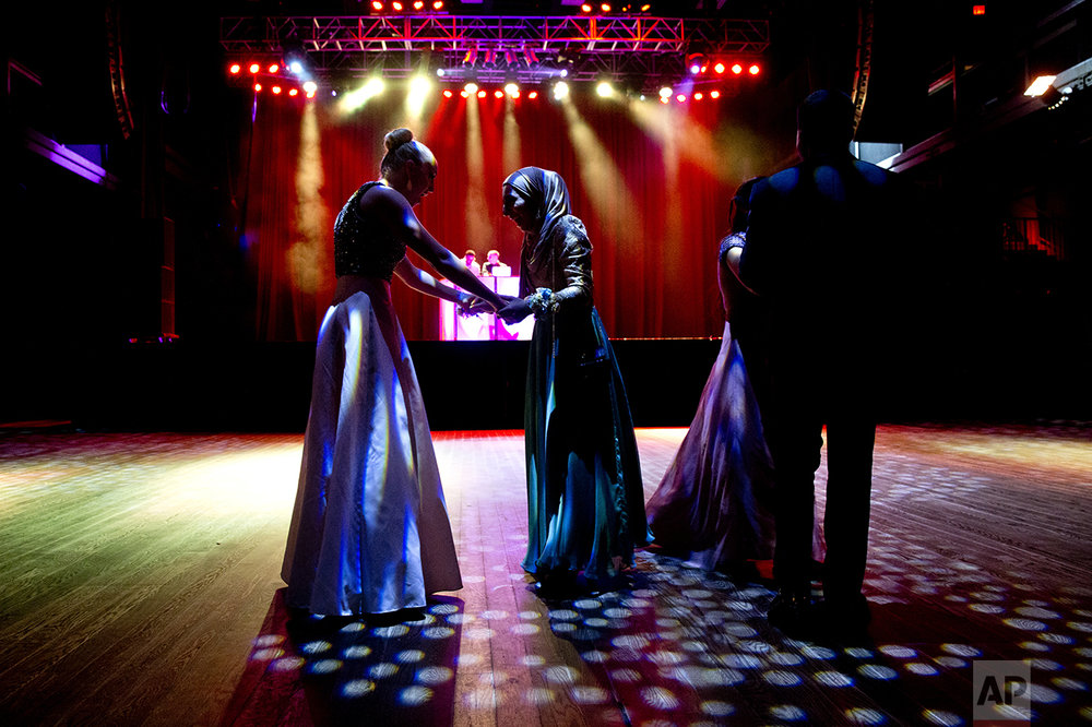 Samantha Bischoff, left, compliments Hannah Shraim on her prom dress during Northwest High School's senior prom at the Fillmore Theater in Silver Spring, Md., on Friday, May 13, 2016. (AP Photo/Jacquelyn Martin)