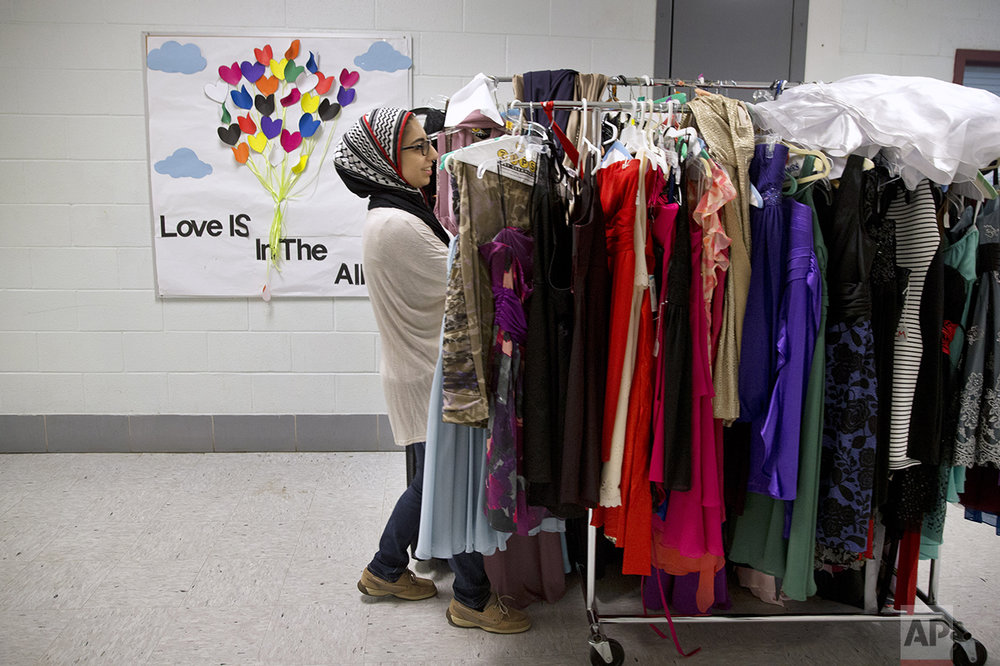 Hannah Shraim, 17, helps to move prom dresses for a fundraiser at Northwest High School in Germantown, Md., Tuesday, May 10, 2016. (AP Photo/Jacquelyn Martin)