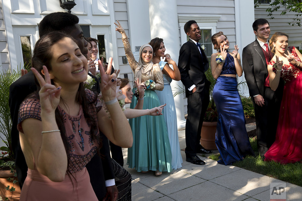 "Hannah Shraim, center, playfully poses with Ashley Riddle, right, as their prom group poses for a ""fun"" photograph for their parents in Germantown, Md., before attending their senior prom for Northwest High School, Friday, May 13, 2016. Shraim and Riddle both went to prom solo while the others in the group brought dates. Shraim ordered her prom dress from a Turkish website that specializes in modest fashion. (AP Photo/Jacquelyn Martin)"