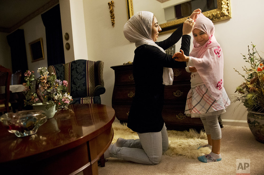 Hannah Shraim, 17, left, fixes a scarf around Lana Algamil, 5, after the little girl asked Hannah if she could try one on before evening prayers at the Shraim family home in Germantown, Md., Friday, May 6, 2016. (AP Photo/Jacquelyn Martin)
