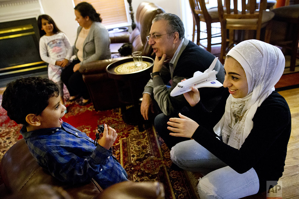 Hannah Shraim, 17, right, plays with Karim Algamil, 5, next to her father Ihab Shraim, at the Shraim family home in Germantown, Md., Friday, May 6, 2016. (AP Photo/Jacquelyn Martin)
