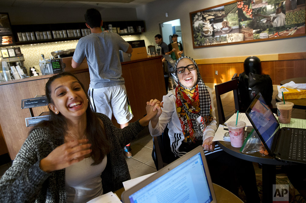 Hannah Shraim, 17, right, jokes with Mekhala Rao, 17, while studying for their final exams at a Starbucks in Germantown, Md., Tuesday, May 10, 2016. (AP Photo/Jacquelyn Martin)