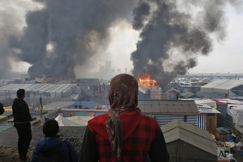 "People stand on a hill as smoke and flames rise from tents, after fires were started in the makeshift migrant camp known as ""the jungle"" near Calais, northern France, Wednesday, Oct. 26, 2016. French authorities declared Wednesday they had cleared out the camp after most of its thousands of residents were driven away on buses — an evacuation accelerated because some of the frustrated, departing migrants set fire to parts of the burgeoning slum. (AP Photo/Thibault Camus)"