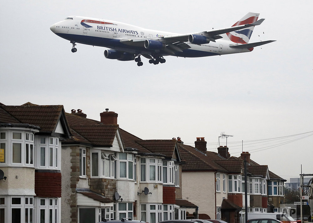 A plane flies over nearby houses as it approaches for landing at Heathrow Airport in London on Tuesday, Oct. 25, 2016. On Tuesday, Britain's government gave the go-ahead to build a new runway at the airport despite concerns about air pollution, noise and the destruction of hundreds of homes in the capital's densely populated western neighborhoods. (AP Photo/Frank Augstein)