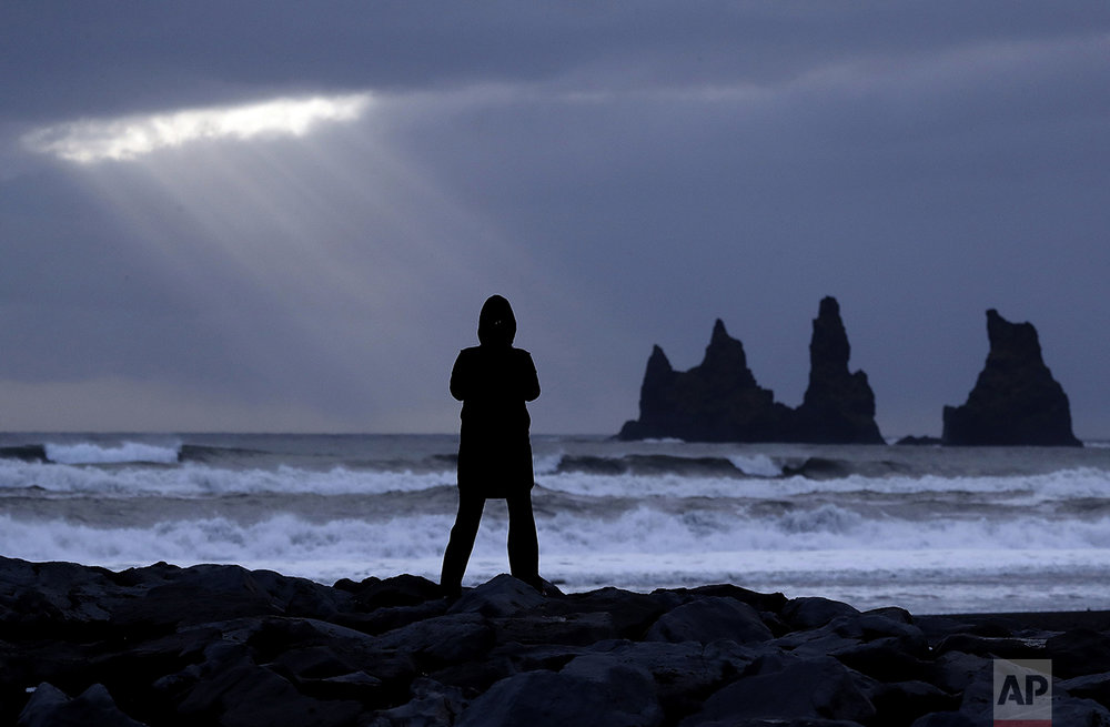 The sun shines through clouds as a woman stands on a black sand beach in Vik, Iceland, near the Volcano Katla, on Friday, Oct. 28, 2016. (AP Photo/Frank Augstein)