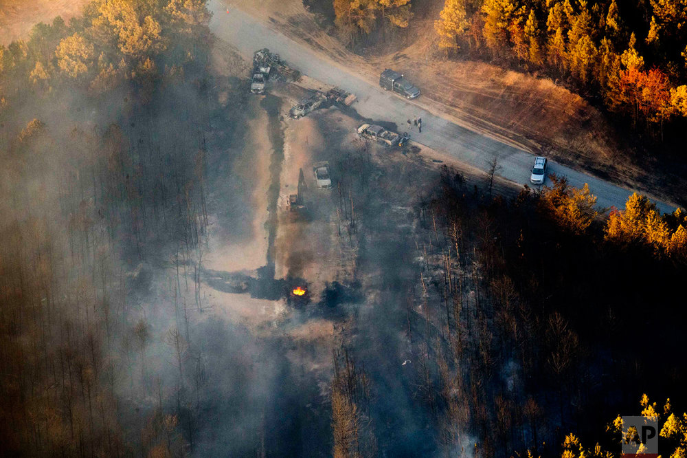 A flame continues to burn after a Monday explosion of a Colonial Pipeline, Tuesday, Nov. 1, 2016, in Helena, Ala. The blast, which sent flames and thick black smoke soaring over the forest, happened about a mile west of where the pipeline ruptured in September, Gov. Robert Bentley said in a statement. (AP Photo/Brynn Anderson)
