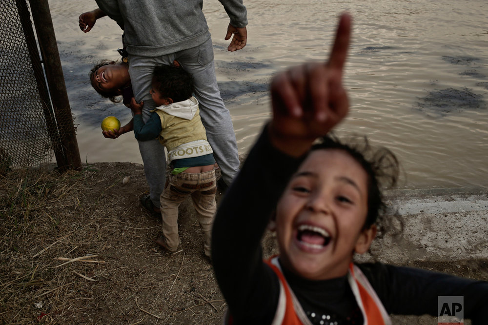 An Egyptian man and children who live on Dahab Island play in front of the Nile River as the water appears a murky brown color due to flooding in southern provinces, in Cairo, Egypt, Tuesday, Nov. 1, 2016. The Nile's water this week turned a murky brown-yellow color, the result of days of heavy rain in parts of the country and subsequent flooding that eroded the surface of lime hills and mountains and swept them into the waterway. (AP Photo/Nariman El-Mofty)