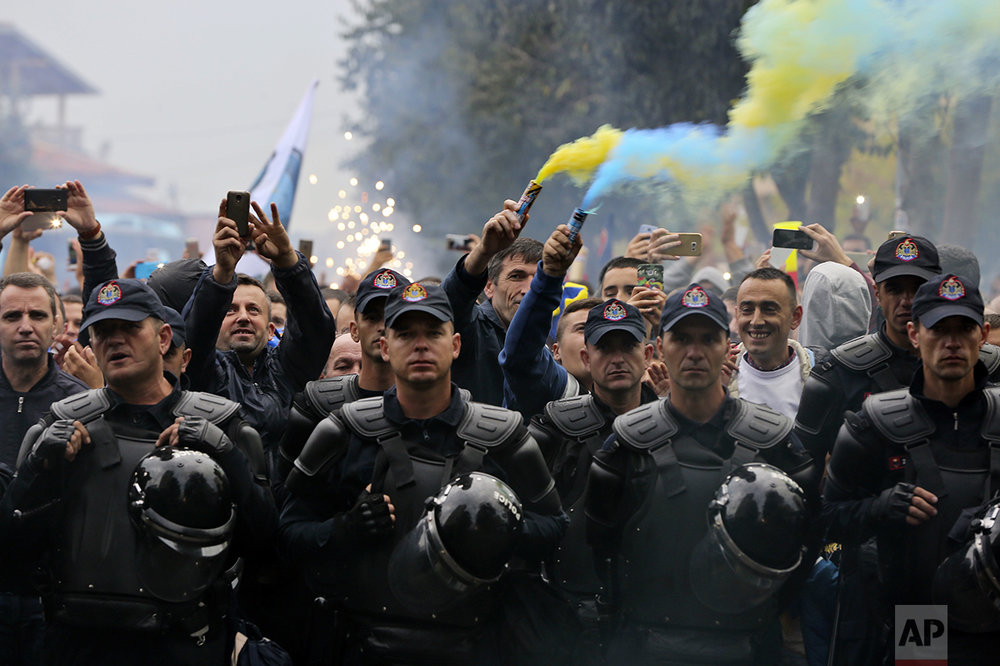 """Members of """"Dardanet"""", a Kosovo fan club, are escorted by police as they celebrate the group's arrival, before the World Cup Group I qualifying soccer match between Croatia and Kosovo in Shkoder, Albania, Thursday Oct. 6, 2016. (AP Photo/Visar Kryeziu)"""