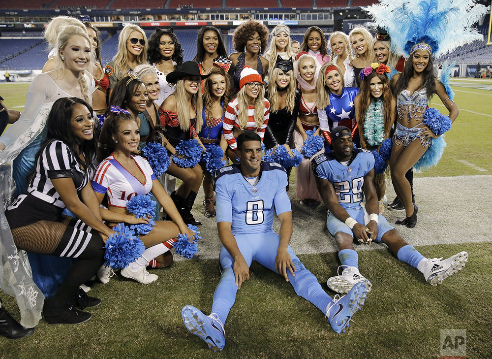 Tennessee Titans quarterback Marcus Mariota (8) and running back DeMarco Murray (29) pose with Titans cheerleaders dressed in Halloween costumes after an NFL football game against the Jacksonville Jaguars Thursday, Oct. 27, 2016, in Nashville, Tenn. The Titans won 36-22. (AP Photo/James Kenney)