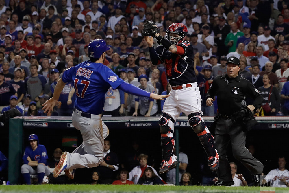 Chicago Cubs' Kris Bryant is safe at home as Cleveland Indians catcher Roberto Perez puts on a late tag during the fourth inning of Game 7 of the Major League Baseball World Series Wednesday, Nov. 2, 2016, in Cleveland. (AP Photo/Matt Slocum)