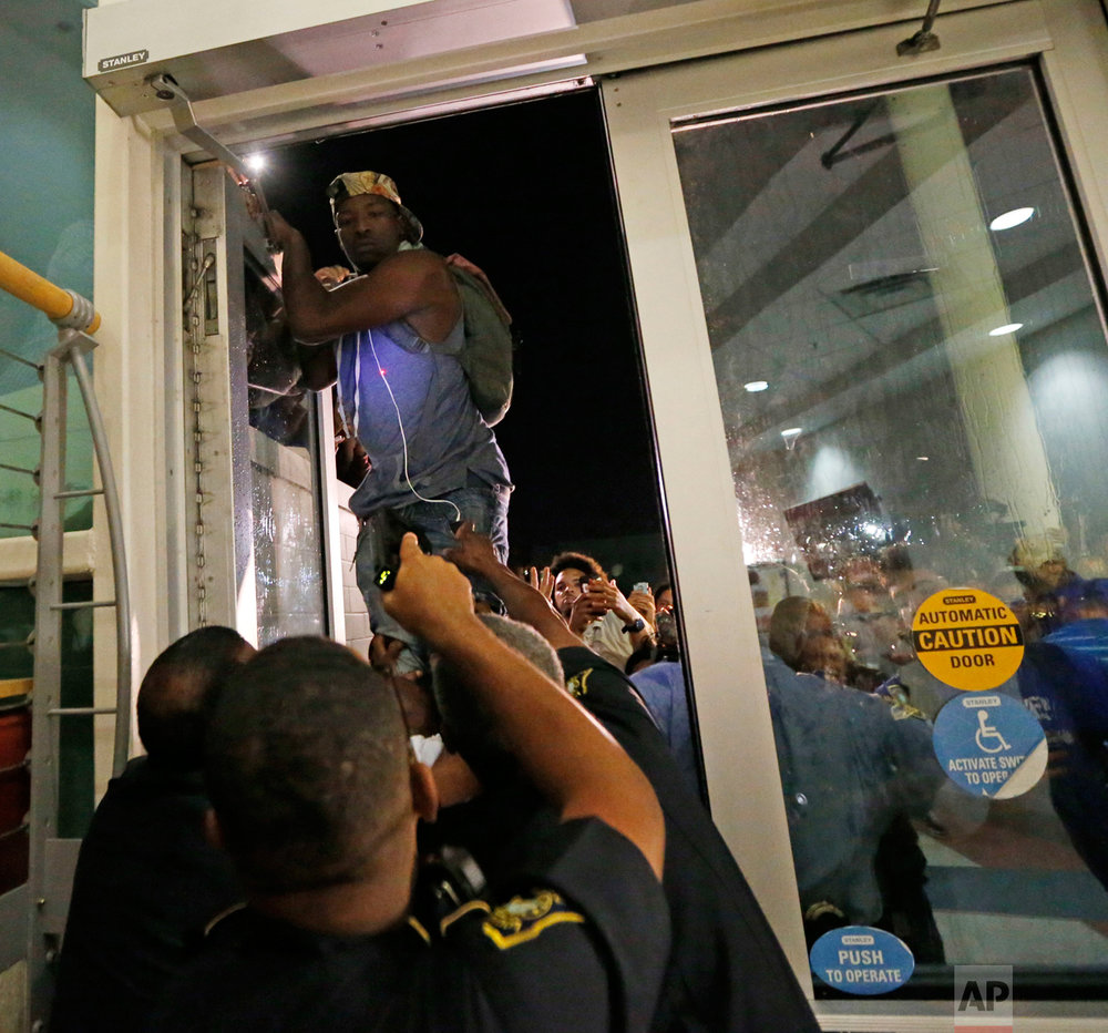 A police officer, front, points a taser as a protester jumps on a door, whole police officers try to keep out protesters against the former Ku Klux Klan leader and current senate candidate David Duke, before a debate for Louisiana candidates for the U.S. Senate, at Dillard University in New Orleans, Wednesday, Nov. 2, 2016. The top five candidates, including Duke, who are running for Louisiana's soon-to-be-vacant U.S. Senate seat are meeting for their last debate ahead of next week's election, at the historically black university. (AP Photo/Gerald Herbert)