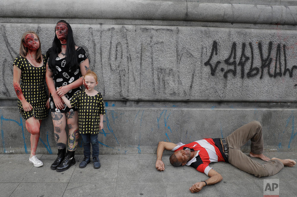 A family in zombie costumes pose for a picture as a man sleeps on the sidewalk at the Zombie Walk in Sao Paulo, Brazil, Wednesday, Nov. 2, 2016. Participants commemorated the Day of the Dead with the annual Zombie Walk. (AP Photo/Andre Penner)