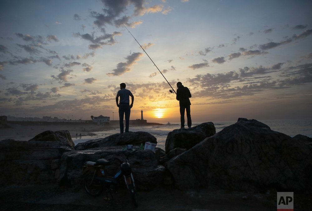 Fishermen wait for a catch on Rabat beach, Morocco, on Wednesday, Nov. 2, 2016. Rabat beach is a hub for families, couples and fitness enthusiasts especially on temperate days.  (AP Photo/Mosa'ab Elshamy)