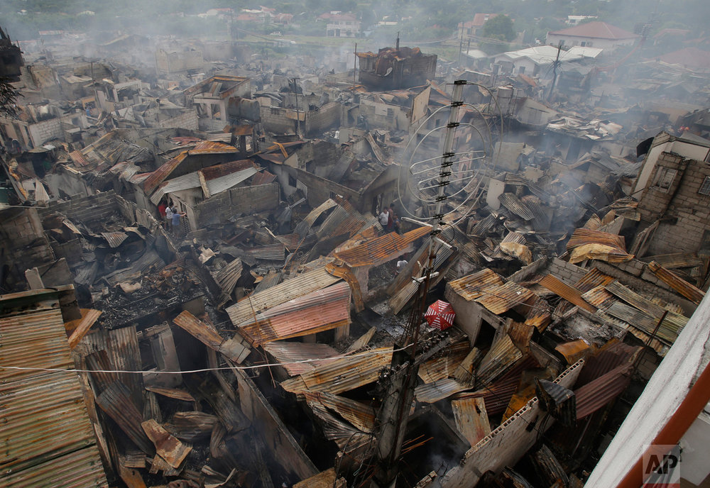 Residents salvage items from smoldering homes after a fire gutted a neighborhood in Las Pinas, south of Manila, Philippines, on Wednesday, Nov. 2, 2016. Las Pinas Fire Marshall Chief Inspector Ramon Capundag said about 800 houses were razed by the fire and left more than a thousand families homeless. (AP Photo/Aaron Favila)
