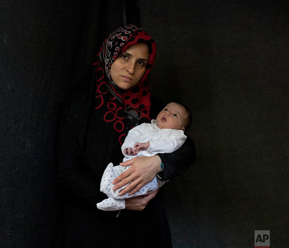 In this Saturday, Oct. 29, 2016 photo 27-year-old Nofa Bashar, a Syrian mother from Aleppo, poses with her baby girl Evelina Bashar in a tent made of blankets given by UNCHR at the Ritsona refugee camp in Greece. Nofa is one of the hundreds of refugee women who gave birth while stranded in Greece. Evelina, the family's sixth child, was born on Monday, Oct. 24, 2016 in the hospital of Chalkida. (AP Photo/Petros Giannakouris)