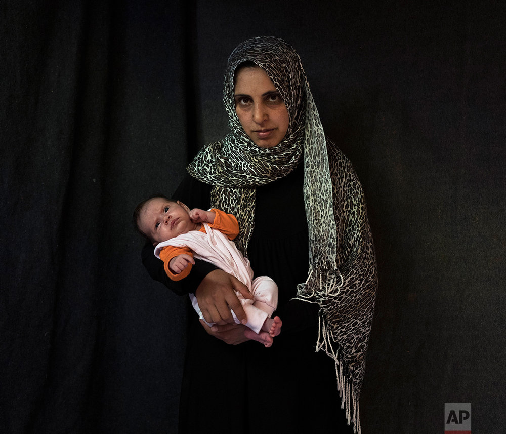 In this Tuesday Sept. 13, 2016 photo 35-year-old Siha Hamnad, a Syrian mother from Al Qunaytirah, poses with her baby girl Mona Alzaour in a tent made of blankets given by UNCHR at the Ritsona refugee camp in Greece. Siha is one of the hundreds of refugee women who gave birth while stranded in Greece. Mona, the family's fourth child, was born on Sunday, July 31, 2016 in the hospital of the nearby town of Chalkida. (AP Photo/Petros Giannakouris)