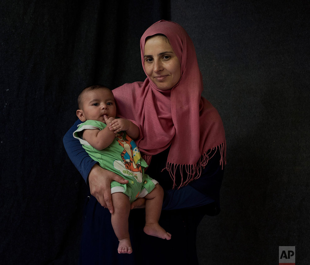 In this Tuesday Sept. 13, 2016, 39-year-old, Hanan Halawa, a Syrian mother from the city of Idlib poses with her baby boy Ahmad Hanash in a tent made of blankets given by the UNCHR at the Ritsona refugee camp in Greece. Hanan is one of the hundreds of refugee women who gave birth while stranded in Greece. Ahmad, the family's fourth child, was born on Sunday, July 10, 2016 in the hospital of the nearby town of Chalkida. (AP Photo/Petros Giannakouris)
