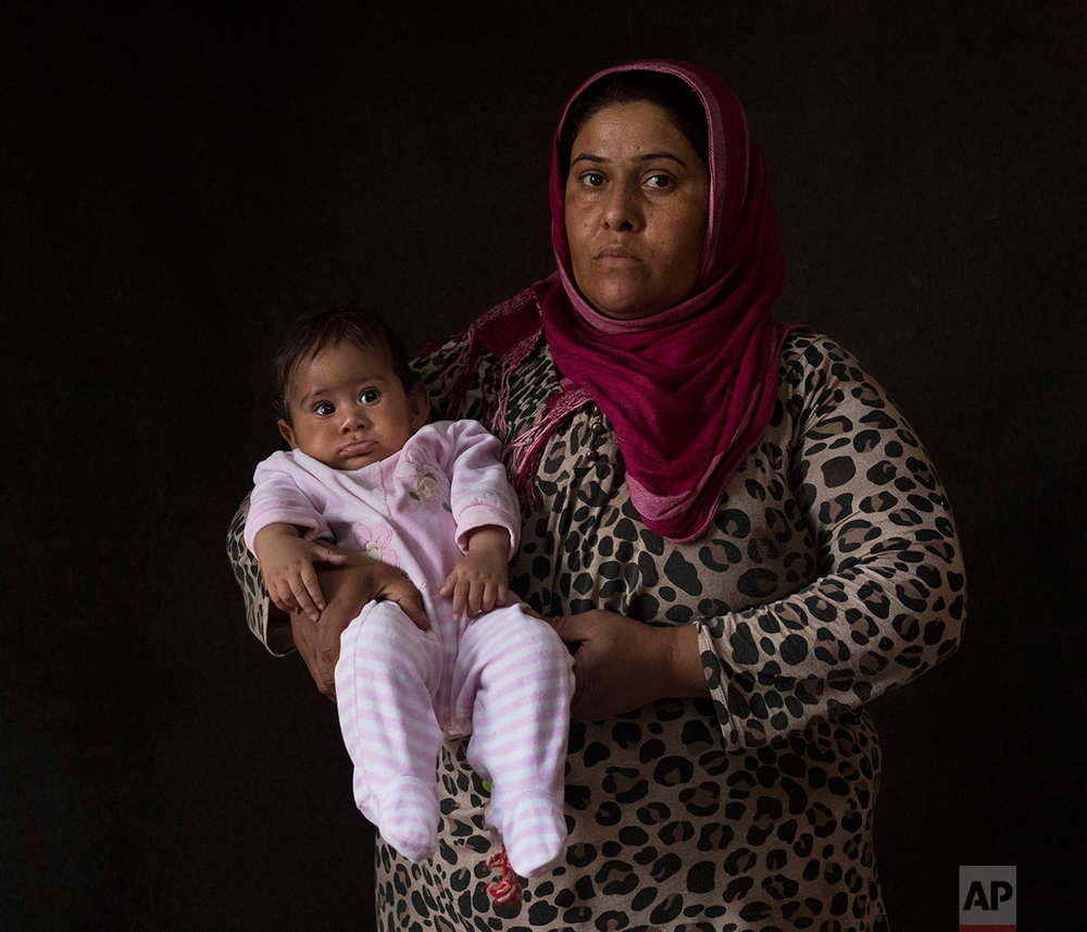 In this Thursday Sept. 22, 2016 photo 35-year-old Najlaa Khalil Tamo, a Syrian mother from Al Hasakah, poses with her baby girl Ritsona Khalil Isa, in a tent made of blankets given by UNCHR at the Ritsona refugee camp in Greece. Najlaa is one of the hundreds of refugee women who gave birth while stranded in Greece. Ritsona, named after the camp, is the family's sixth child and was born on Wednesday, March 31, 2016 in the hospital of the nearby town of Chalkida. She spent the first few weeks of her life in and out of hospital after doctors found a serious birth defect in her lower spine that has paralyzed her from the waist down. Doctors said she will never be able to walk. (AP Photo/Petros Giannakouris)