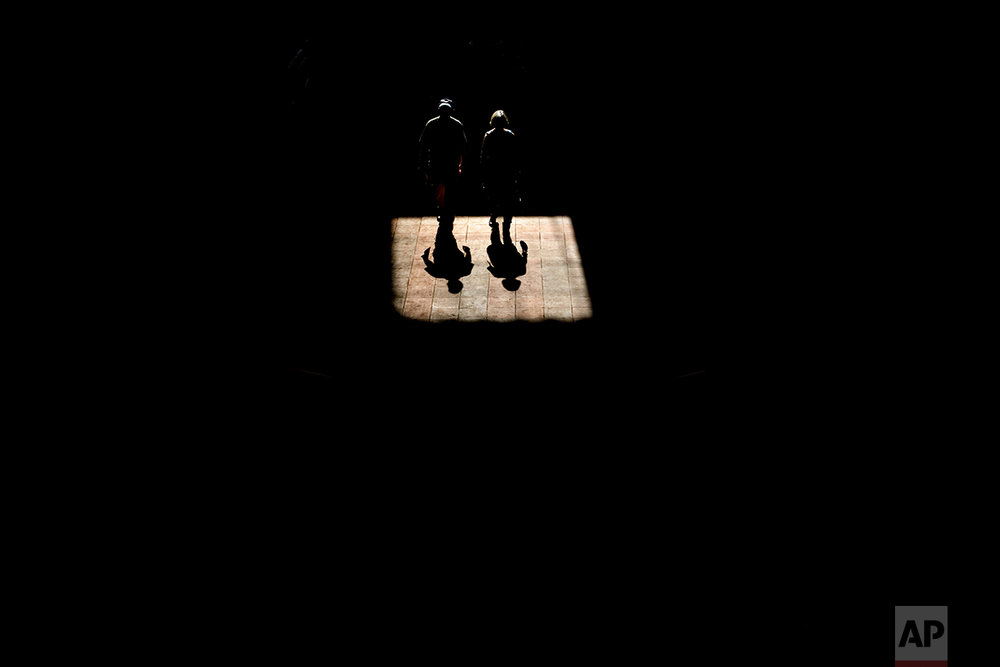 Two fans walk through a shaft of light at the Breeders' Cup horse races at Santa Anita Park, Friday, Nov. 4, 2016, in Arcadia, Calif. (AP Photo/Jae C. Hong)