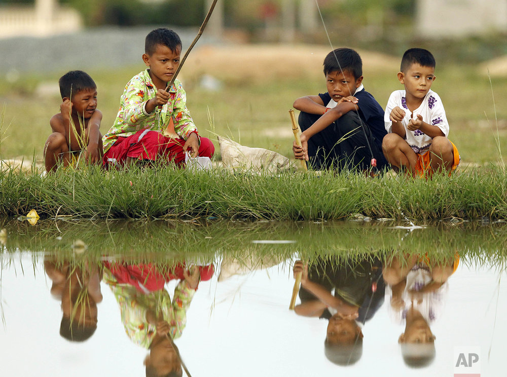 Boys use a fishing pole in the flooded village of Samaki on the outskirts of Phnom Penh, Cambodia, Monday, Oct. 31, 2016. About 18 provinces have suffered flood damage after heavy rain that affected thousand hectares of rice fields, according to the Cambodian Agriculture Ministry. (AP Photo/Heng Sinith)